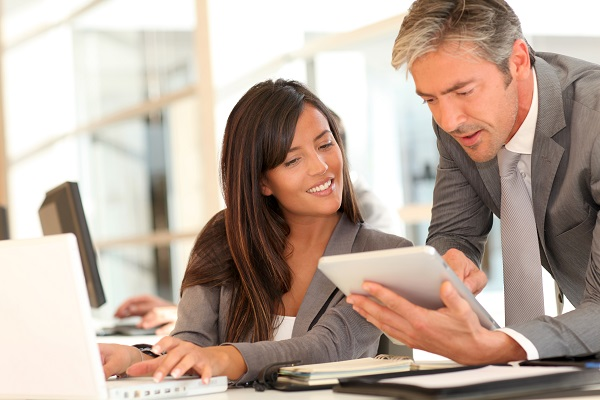 older man in gray suit showing younger woman in suit something on tablet in office environment